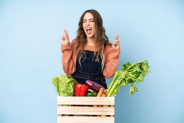 Boer met vers geplukte groenten in een doos met vingers gekruist