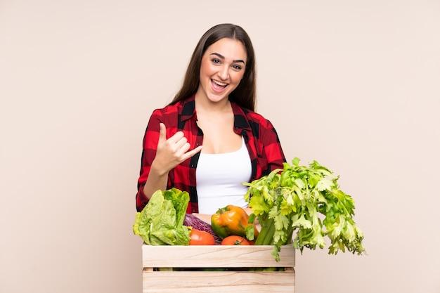 Boer met vers geplukte groenten in een doos