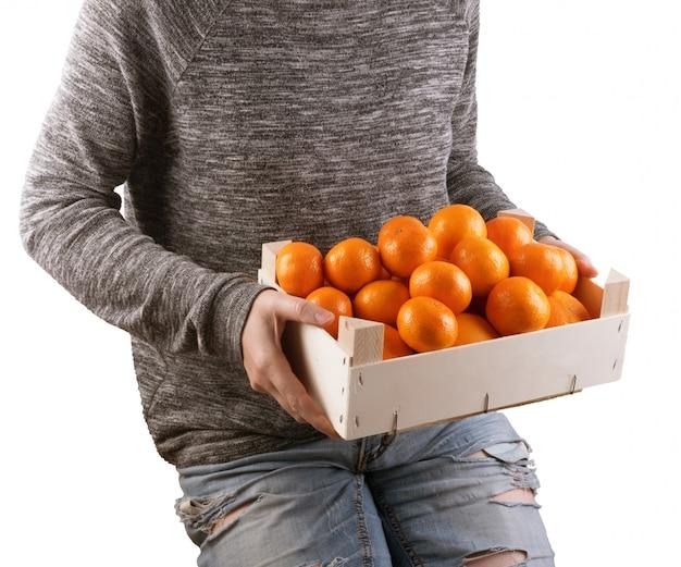 Boer met verse mandarijnen of mandarijnen in houten kist