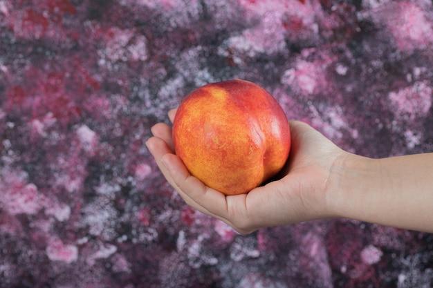 Boer of verkoper die een rode perzik in de hand houdt.