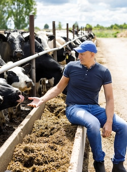 Boer op boerderij met melkkoeien