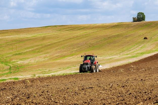 Boer op een tractor ploegt het land voordat hij met een zaaibedcultivator zaait