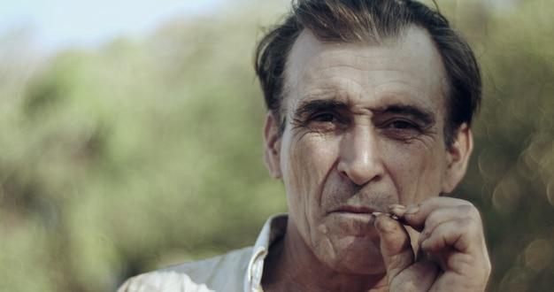 Boer rookt een sigaret op de boerderij, stro sigaret