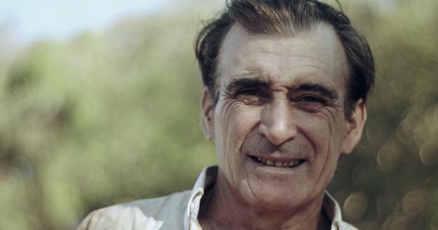 Boer van middelbare leeftijd op landbouwgrond glimlachend kijkend naar de camera