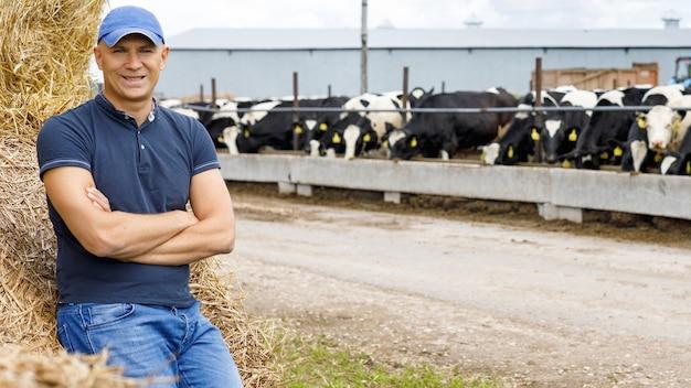 Boer werkt op de boerderij met melkkoeien