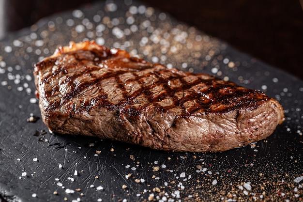 Boerderij biologisch voedsel concept. gegrilde biefstuk met grill. gebakken biefstuk op zwarte lei, op een zwarte achtergrond.