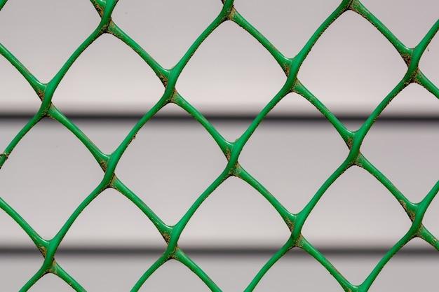 Boerderij van gevelbeplating door het hek met kettingschakel dat in focus is