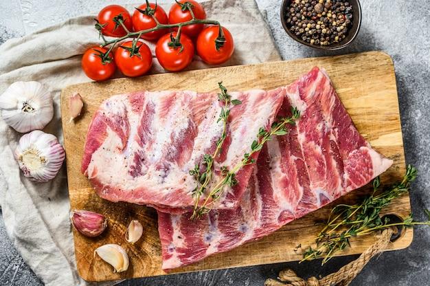 Boeren biologisch vlees. rauwe varkensribbetjes met rozemarijn, peper en knoflook. grijze achtergrond. bovenaanzicht