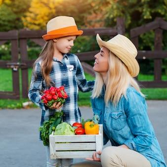 Boeren moeder en kind houden een doos met groenten