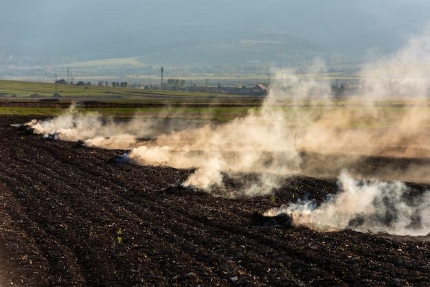 Boeren verbranden het droge gras en de strostoppels op het veld in de herfst, een andere oorzaak van de opwarming van de aarde.