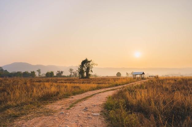 Boerenhut midden op de prairie bij zonsopgang.