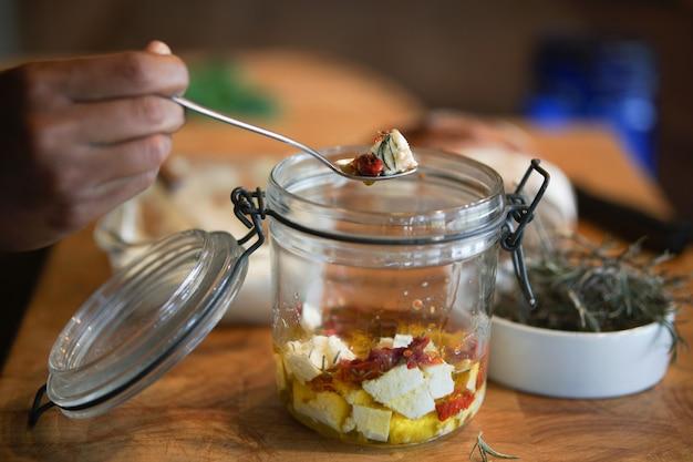 Boerenkaas, zongedroogde tomaten en rozemarijn gemarineerd in olijfolie in glazen pot. vegetarisch eten