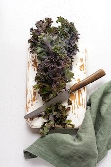 Boerenkool laat vers groen gekruld achter op een snijplank op een lichtgrijze leisteen, steen of betonnen ondergrond. selectieve aandacht. gezond vegetarisch eten.
