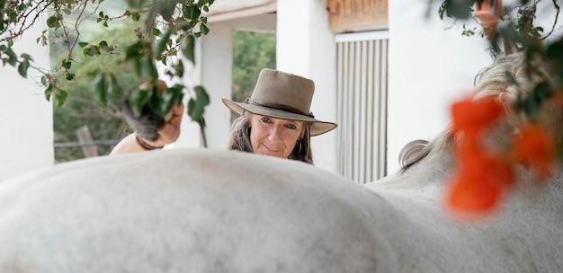 Boerin die haar paard borstelt op de boerderij