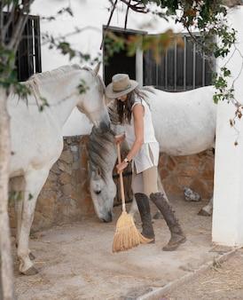 Boerin die haar paardenstallen schoonmaakt