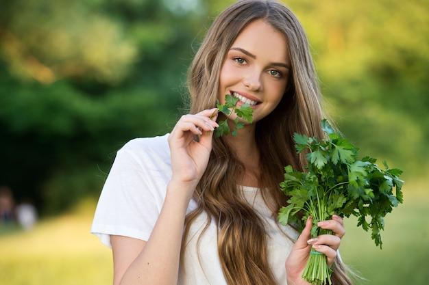 Boerin houdt gekweekte verse groenten. oogst van de boerderij. jonge vrouw met een bosje peterselie.