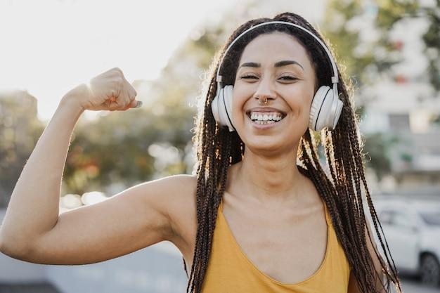 Boheemse afrikaanse meid luistert afspeellijstmuziek met koptelefoon - focus on face