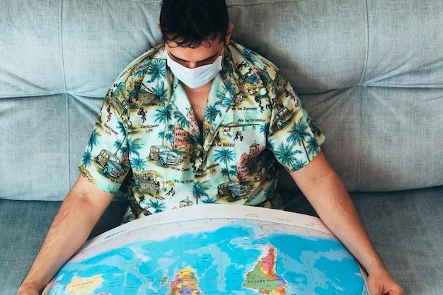 Boheemse man met masker op zijn gezicht die op zijn bank naar een kaart van de wereld kijkt, gekleed in een hawaiiaans shirt en spijkerbroek. een nieuwe bestemming kiezen om opnieuw te reizen. coronapandemie
