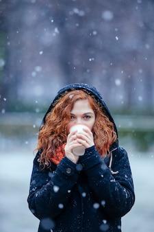 Boheemse vrouw die een kop thee houdt onder de sneeuw