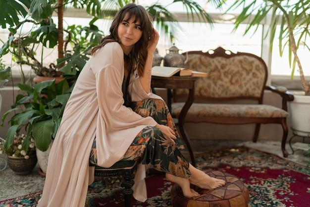 Boheemse vrouw in elegante huiskleding die 's ochtends in een stijlvolle woonkamer geniet.