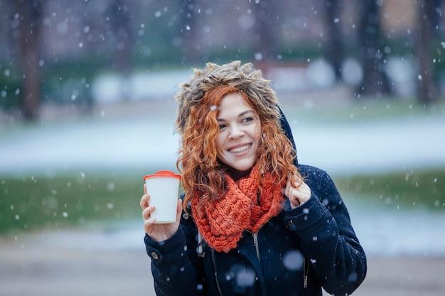 Boheemse vrouw koffie drinken onder de sneeuw