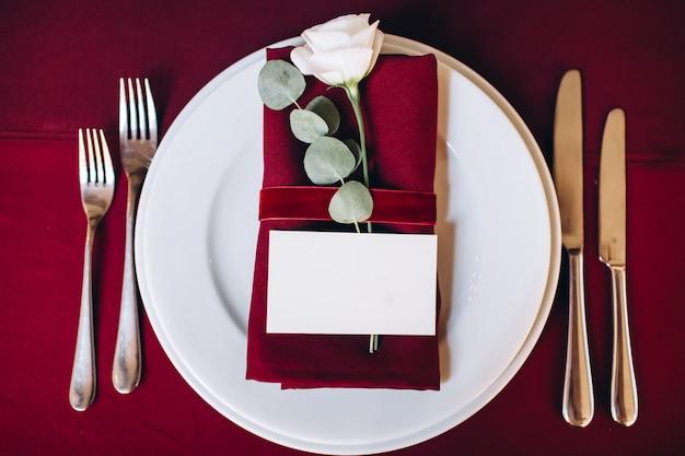 Boho bruiloft decor. feestelijke tafel met bordeauxrood tafelkleed. decoratie van de hallenkrans met gloeilampen.