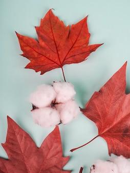 Boho-compositie van rode esdoornbladeren en katoen.