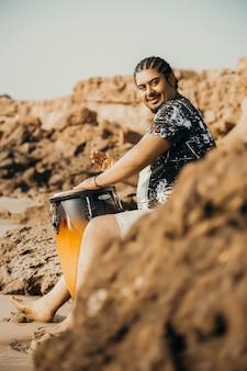 Boho musucian in een verlaten strand met zijn trommel