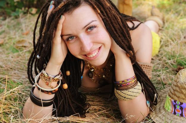 Boho-stijl lachende vrouw portret, meisje veel plezier buiten in herfst zonnig park liggen