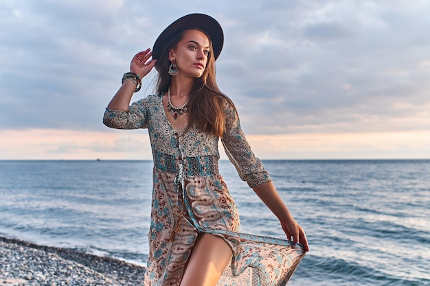 Boho vrouw in lange jurk en vilten hoed