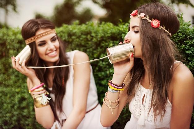 Boho-vrouwen praten met tin kunnen bellen