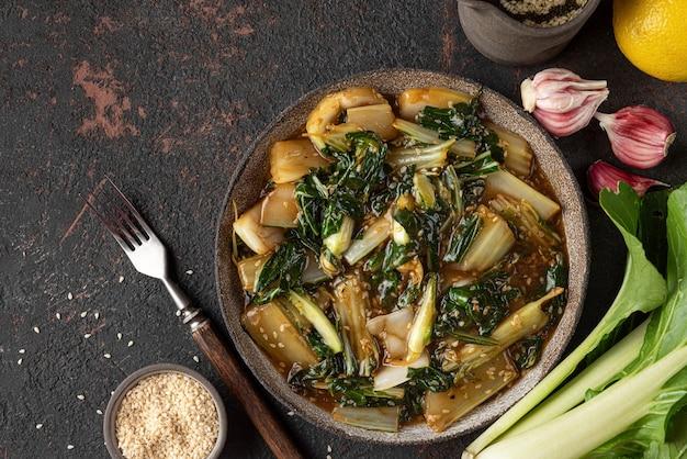 Bok choy groenten roerbak met sojasaus en sesamzaadjes op donkere achtergrond. chinese keuken. bovenaanzicht