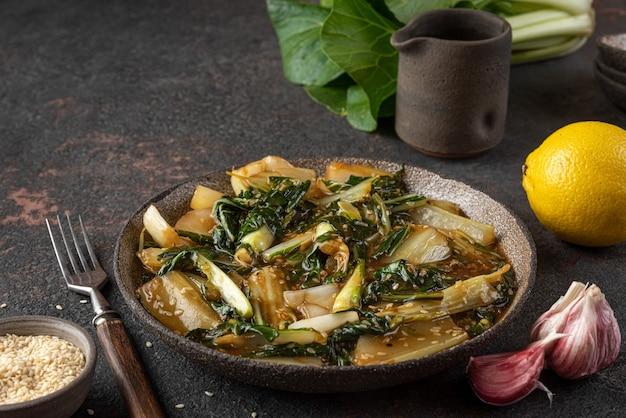 Bok choy groenten roerbak met sojasaus en sesamzaadjes op donkere achtergrond. chinese keuken. gezond veganistisch eten. detailopname