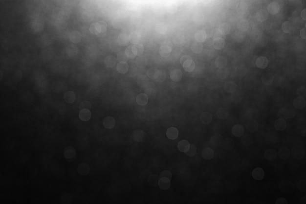 Bokeh van lichten op zwarte achtergrond met lichte vlek op centrumbovenkant voor bekleding
