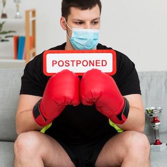 Boksen evenement uitgesteld bericht gehouden door man met een medisch masker