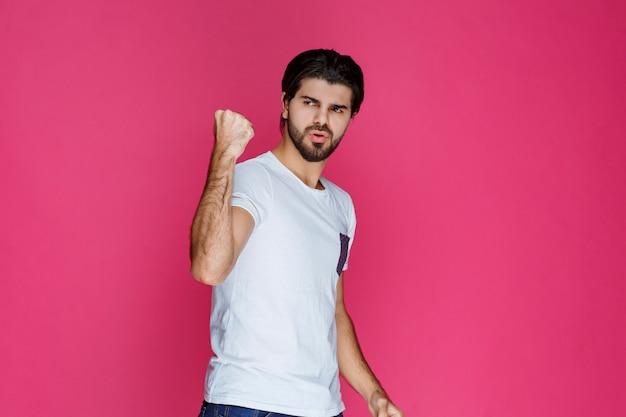Boksen man toont zijn vuisten en maakt punt op zijn kracht.