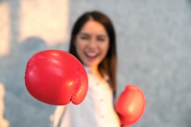 Boksen zakelijke vrouw ponsen richting camera dragen van bokshandschoenen.
