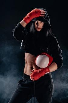 Boksende vrouw in zwarte hoodie vóór gevecht