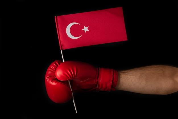 Bokser die de vlag van turkije op zwarte achtergrond houdt.