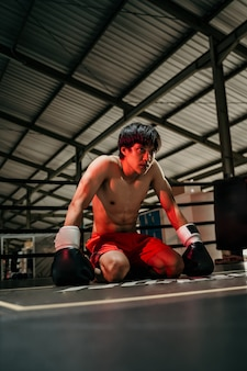 Bokser vechter in bokshandschoenen zit op de vloer van de ring