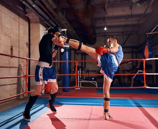 Boksers trainen kickboksen in de ring bij de healthclub