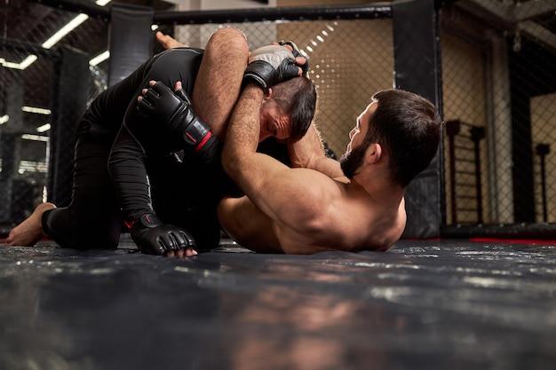 Boksersvechters vechten zonder regels in de ring-achthoek. shirtloze vechter maakt wurgende ontvangst, gaat winnen, atletische sportieve man tijdens mma