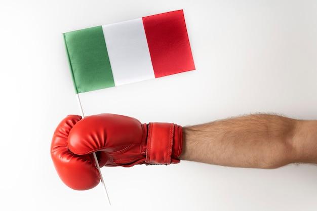 Bokshandschoen met italiaanse vlag. bokser houdt vlag van italië. witte muur.
