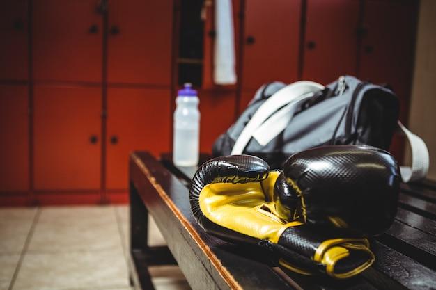 Bokshandschoenen op bankje in de kleedkamer