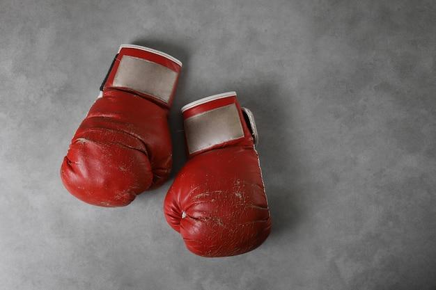 Bokshandschoenen op de sportschoolvloer na de training. grijze grunge concrete achtergrond.