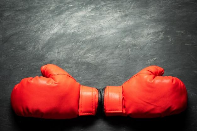 Bokshandschoenen op zwarte cementachtergrond. concept van vechten of boksen.