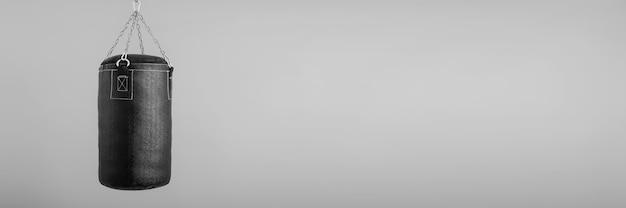 Bokszak die op grijs, bannerachtergrond hangen