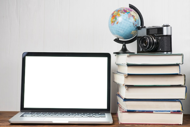 Bol en camera op boeken dichtbij laptop