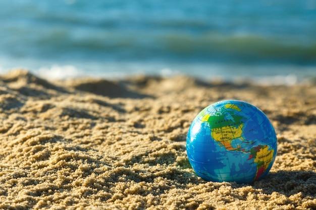Bol van de aarde op een zandig strand op een oceaanachtergrond.