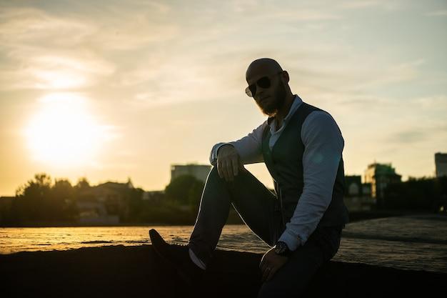 Bold guy met een stijlvolle baard en zonnebril op een wazige stad tijdens dramatische zonsondergang. concept van succes en wil